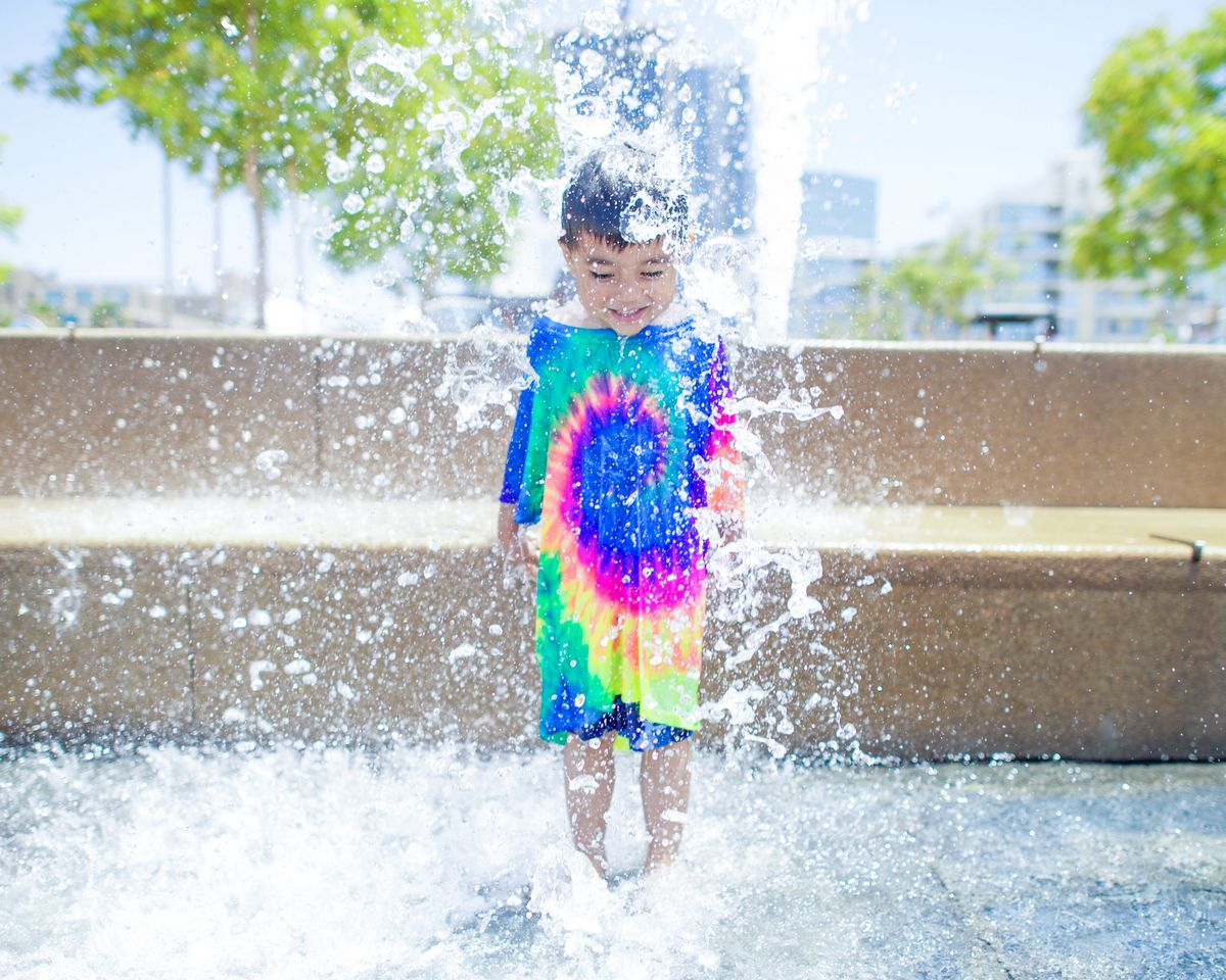 A child jumping on a splash pad in the city.